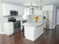 white kitchen with stainless appliances and earth tones