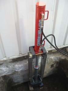 photo of hydraulic machine to push steel foundation repair piers into the ground