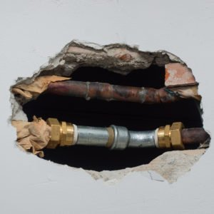 photo of plumbing through hole in wall
